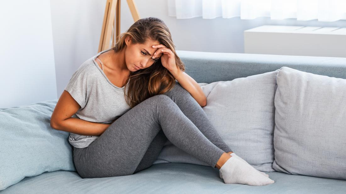 a woman in pain holding her pelvis because she has pelvic floor dysfunction